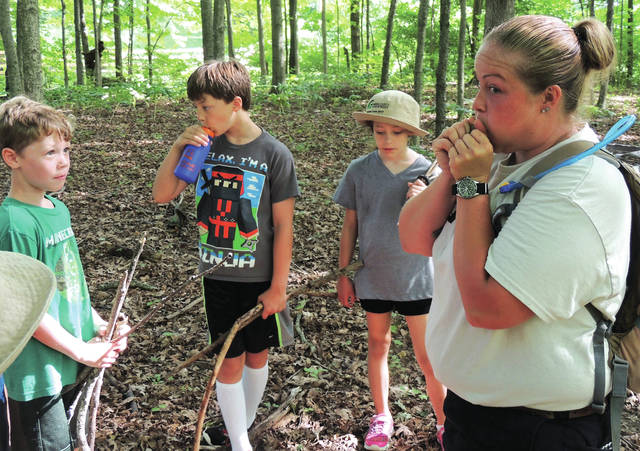 "Submitted photos Greene County Parks and Trails' Minecraft Camp had campers digging for minerals, crafting their own diamond swords and using a bow and arrow while in ""survival mode."" GCP&T Naturalist Ashlee Schmitt, pictured, demonstrates how to make a whistle out of an acorn."