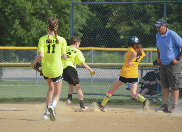Not even speedy Minion socks could get this Extreme's One-Hour Heating & Air Conditioning-sponsored runner safe on first base, as the Steck & Stevens Custom Lettering defender narrowly gets to first base first, during Friday's June 30 Teen League Beavercreek Youth Softball Association play at Rotary Park.