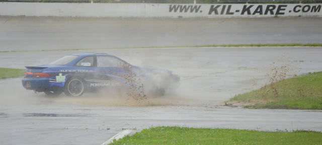 A driver slides his car through an infield mud puddle, during the first day of the No Star Bash, auto drifting event hosted by the Midwest Drift Union June 23 at Kil-Kare Raceway in Xenia.