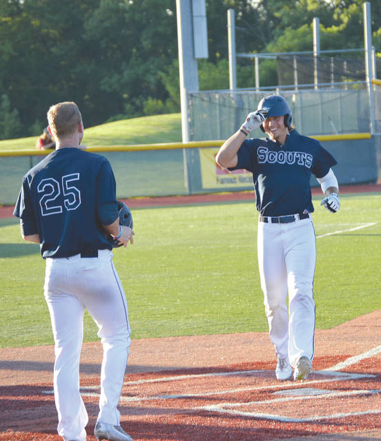 Jordan Lambert (25) greets Kyle Casserly at home plate on Tuesday, July 25 at Xenia's Grady's Field, after Casserly smacked a two-run home run over the right field fence in a 7-3 Xenia Scouts loss to the Hamilton Joes.