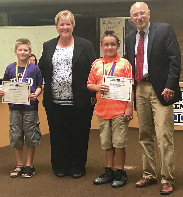 Scott Halasz | Xenia Daily Gazette Malachi Freed (left) and Colton Brown (right) were awarded national honor roll medals for their performance in th Noetic Learning Math Contest. They were honored during the July 10 school board meeting and are pictured with board president Pam Callahan and Superintendent Denny Morrison.