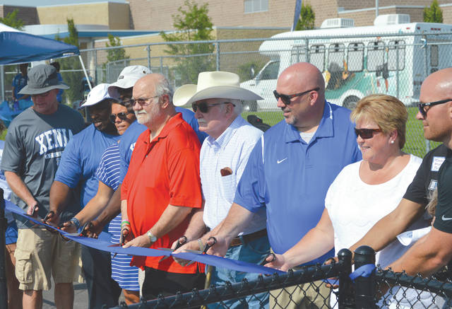 Xenia High School and Xenia Community Schools district officials participate in a ceremonial ribbon cutting to mark the opening of the district's brand new track facility, July 12 at Doug Adams Stadium in Xenia.