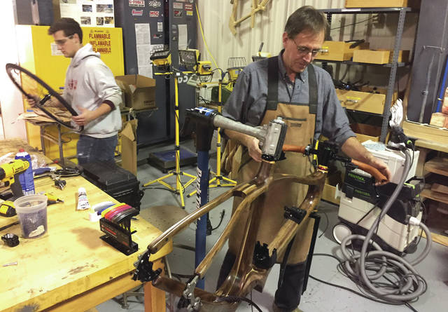 Submitted photos Cedarville University professor Jay Kinsinger, who designed and built the wooden frame for the Bike of the Future, works on the handlebars.