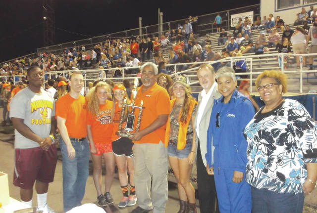 In a photo taken from the 2015 Backyard Battle when the game was last held in Xenia, Beavercreek City Councilman Brian Jarvis (center) holds the Backyard Battle Trophy. He's joined by Beavercreek Kiwanis President Jason Hallmark, Beavercreek Rotary President Dick Gould, Xenia Mayor Marsha Bayless, Rev. Gloria Dillon of Glory Ministries Church-Xenia, and several Xenia/Beavercreek High School Student Council Members.