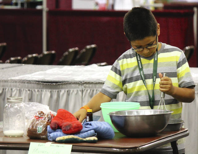 Anna Bolton | Greene County News Matthew Lee, 9, makes french toast during the beginners' division of the baking contest July 31.