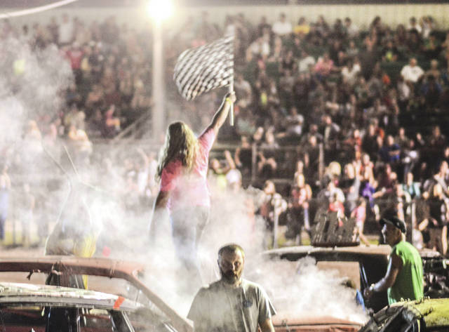 "Cassie Storer of Xenia stands on the hood of her car and waves the checkered flag to the Greene County Fair grandstand crowd, after Monday's July 31 Smash It Demolition Derby. With her friends chanting ""Cassie! Cassie! Cassie!"" Storer won the Street Stocks competition."