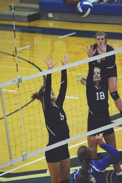 Wilmington players Kaylee Tackett (9) and Riley Flint (18) go up to try and block a left-side hit by Xenia's Saphron Cummins, during the Aug. 21 girls high school volleyball match at Xenia High School. The host Xenia Buccaneers won the match in three sets.
