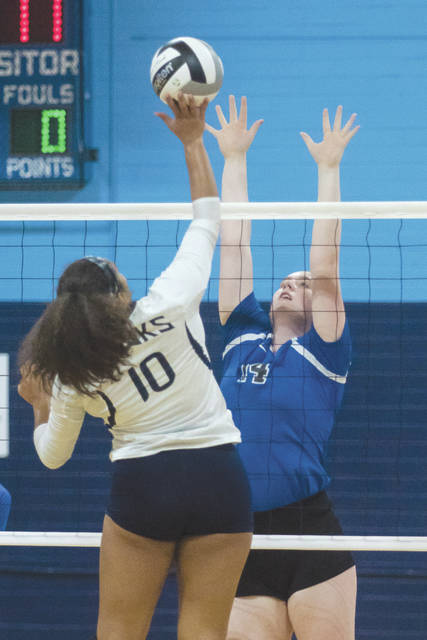 Alex Ronnebaum, Yellow Springs' junior middle blocker, goes up to try and block a shot hit by Fairborn's Jessica Black, during Wednesday's Sept. 20 girls high school volleyball game at Fairborn High School. Yellow Springs won the match in three sets.