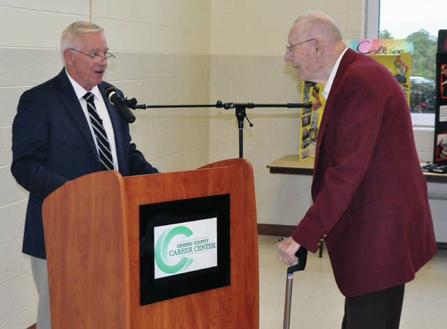 Submitted photos Ohio State Representative Bill Dean presents Wallace Gossett, first director of the Greene County Career Center, with a proclamation Sept. 14 at the GCCC 50th anniversary celebration.