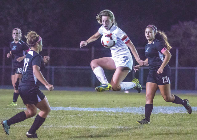 Fairborn's Lauren Thomas leaps to stop a pass, between Xenia players Alyssa Echols (17) and Sofia Castonguay (13), during Wednesday's Oct. 11 girls high school soccer match at Fairborn's Soccer Stadium. The two Greater Western Ohio Conference rivals played to a 1-1 tie.