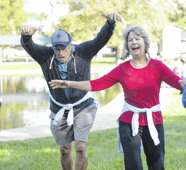 Linda Johnannes shows off her Xenia pride with dollar bills hanging from her ears -- she's a Buck-in-ear -- as she and her husband, Rick, race to the finish line.