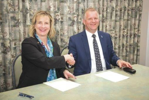 Submitted photo Wright State President Cheryl B. Schrader and Iain Martin, vice chancellor of Anglia Ruskin University, signing a partnership agreement between the two institutions.