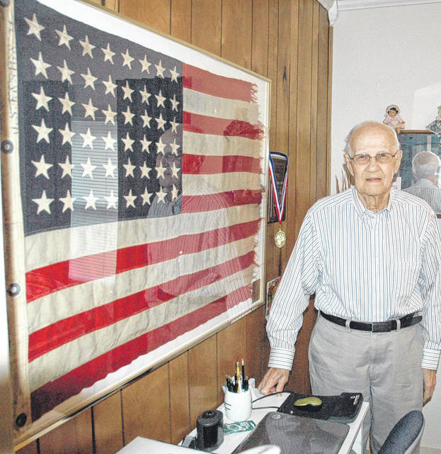 Scott Halasz | Xenia Gazette Beavercreek resident Baylor Kirk shows off the flag that flew over the USS Loy during World War II. He was given the flag and takes it to the yearly reunion.