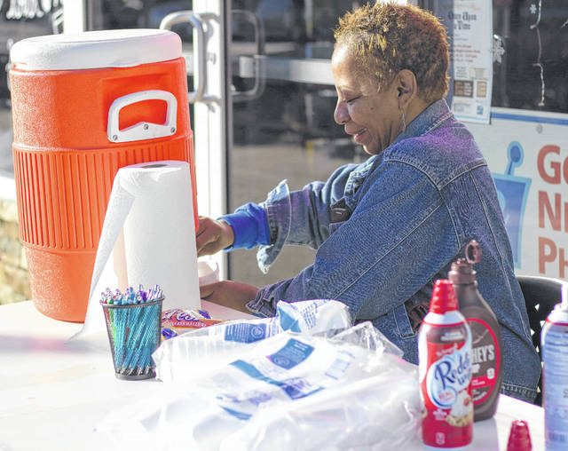 Ms. Lacy offers free hot chocolate outside Barr's Hometown Pharmacy, one of Xenia's newest small business additions.