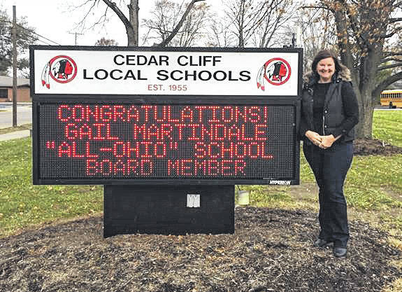 Submitted photo Gail Martindale stands by the Cedar Cliff Local School District reader board acknowledging her recent Ohio School Board's Association honor.