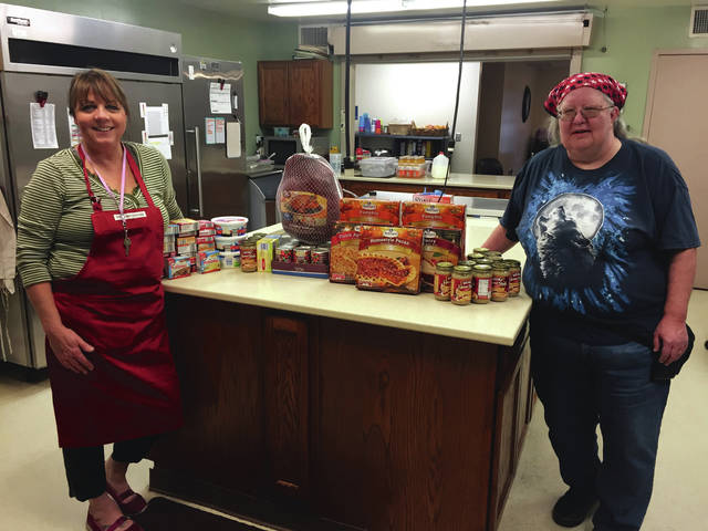 Submitted photo Elissa Wilson, RVT, CPDT-KA at Veterinary Associates, brings Thanksgiving meal items to Debbie Tipton, Family Violence Prevention Center Kitchen Coordinator.