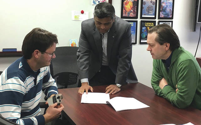 Submitted photo AFRL project researchers Dr. Joseph Slocik (left), Dr. Rajesh Naik, and Dr. Patrick Dennis review the recently-signed licensing agreement that grants locally-based innovators S.A.Wyze exclusive rights to use AFRL-developed Ultra-Stable Antibody Liquids technology for human diagnostic work.