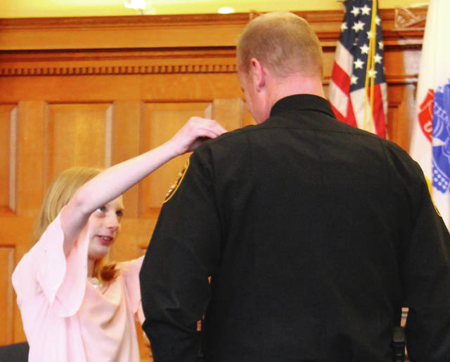 Anna Bolton | Xenia Gazette Courtney Prall pins her father's uniform Jan. 5 in a Greene County Common Pleas courtroom during his swearing-in ceremony. Capt. Shawn Prall was promoted from sergeant to captain within the Greene County Sheriff's Department.