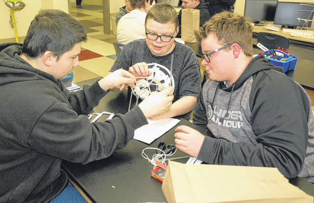 Photos by Scott Halasz | Xenia Daily Gazette Travis Sexton (left), Kaden Harris (center), and Seth McCane (right) work on their building duirng science class at Greeneview Middle School Jan. 25. Students were tasked with erecting a building that could withstand an earthquake, using only a handful of household items like straws and string.