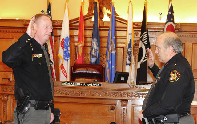 Photos by Anna Bolton | Xenia Daily Gazette Sheriff Gene Fischer gives the oath of office to Capt. Shawn Prall Jan. 5 in a Greene County Common Pleas courtroom. Prall was promoted from sergeant to captain, assuming duties in the road and civil services section.