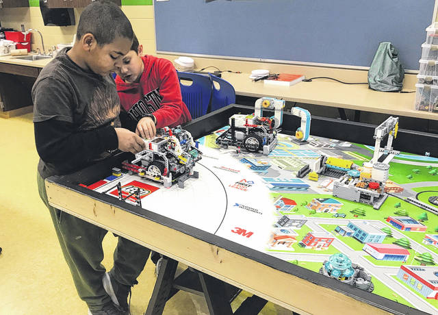 Scott Halasz | Xenia Daily Gazette Malaki Gill (left) and Trey Greene work on their robot during a team practice session Jan. 4. The McKinley Lego robotics team is in the district tournament at Wright State this weekend.