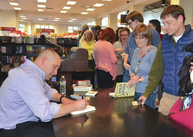 """Submitted photo AFRL Materials and Manufacturing Directorate engineer and author TJ Turner signs copies of his first book, """"Lincoln's Bodyguard,"""" in April 2015."""