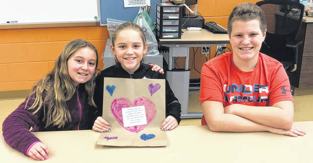 Scott Halasz | Greene County News Tecumseh Elementary School students Ava Wellman, Kyndall Howard, and Gunnar Stephan display a decorated Kroger grocery bag. Students are designing the bags with Valentine's Day themes to help brighten customers' days.