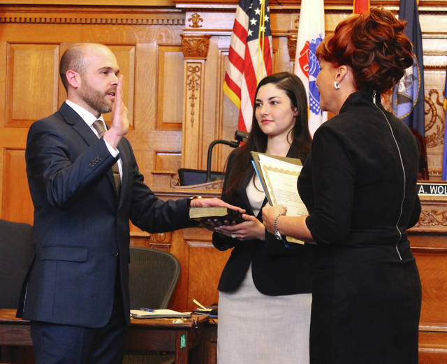Anna Bolton   Greene County News Former Clerk of Courts Terri Mazur administers the ceremonial oath of office to Clerk of Courts AJ Williams with wife Leah during an official swearing-in ceremony Feb. 2 in Greene County Common Pleas Courtroom 1. Williams was actually sworn-in a minute past midnight Jan. 1 when he took office.