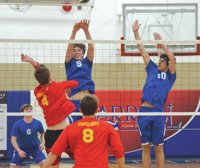 Cameron Provonsil (9) deflects a hit by Taylor Lovely (4) of Purcell Marian, during Tuesday's March 27 boys high school volleyball game at Carroll High School. The host Patriots won their home opener in straight sets, 25-6, 25-6, 25-6.