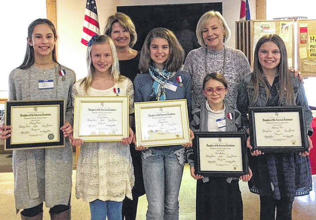 Submitted photos Winners of the American History Essay Contest were presented with a framed certificate and medal: Alayna Allport, First Place; Olivia Augustine, Second Place, Audrey Stanley, Second Place; Mariah Grigsby, Third Place and Hadassah Oliver, Third Place. Not shown is First Place winner Parker Burke. Chapter Chairman Betsy Crandall and Teresa Bauman, sixth grade teacher at Legacy Christian Academy stand behind.