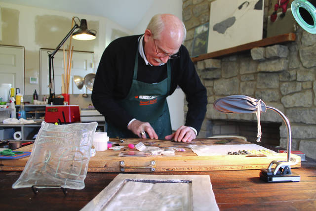 Anna Bolton | Greene County News Don Coakley of Xenia assembles glass beads on his workbench before placing them in a kiln.