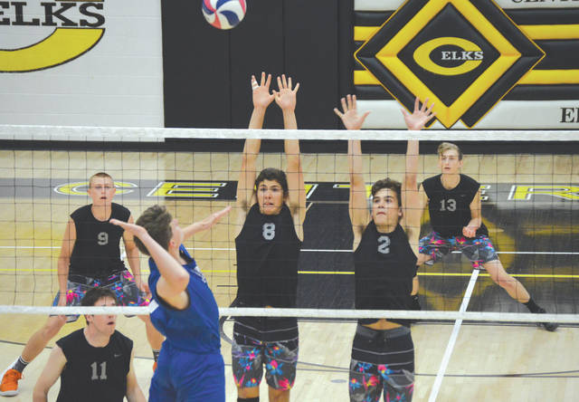 Beavercreek's Riley Bell (8) and Ben Page (2) go up for a block attempt, as Michael Abbitt (11), Jarrod Brown (9) and Simon Ricks (13) look to grab the deflection, in Tuesday's May 22 boys high school volleyball West Regional semifinal match against Miamisburg. Beavercreek won in three sets, on the Centerville High School floor.