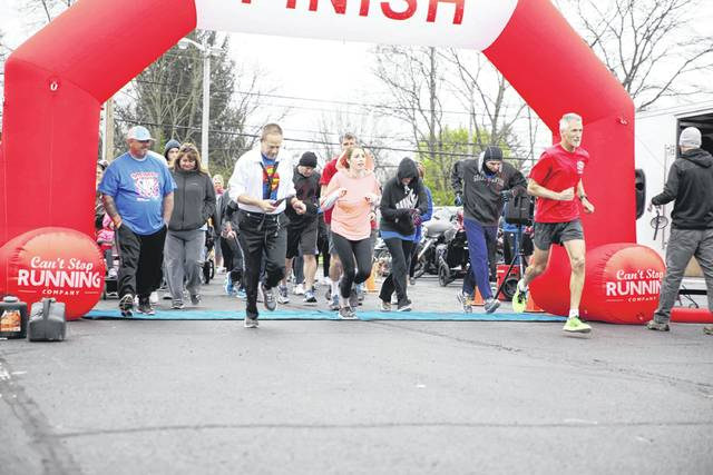 Submitted photo Runners cross the start/finish line of the Superhero Child Abuse Prevention and Elimination (C.A.P.E.) 5K April 28.