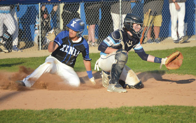 Xenia senior Logan Bilbrey slides safely across home plate with the winning run before the throw from the outfield can get to Fairborn catcher Jacob Moore, in Tuesday's May 7 sectional high school baseball tournament game at Xenia High. Xenia needed extra innings to claim a 2-1 win over Fairborn.