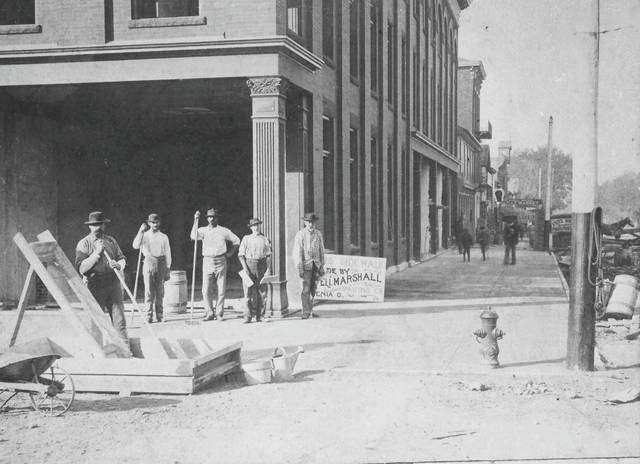 Submitted photo Men pour the new sidewalk at the Allen Building on the southwest corner of Main and Detroit streets circa 1895.