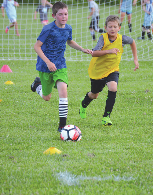 A pair of Bellbrook Soccer Association/Ohio Fusion SC boys head upfield during one of several fun contests held June 20 at the first Open Field event of the season at Sackett-Wright Park in Bellbrook.