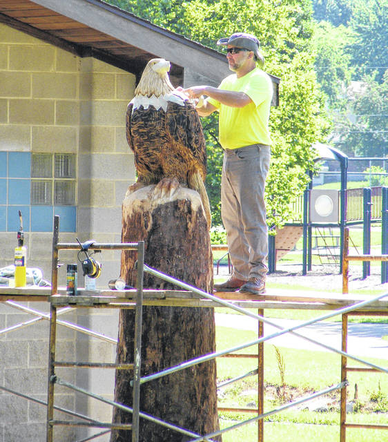 Submitted photos Matt Missey from Ohio Tree Carving in New London works on an eagle at Shawnee Park. The tree was carved into bird as part of the city's adopt a tree program.
