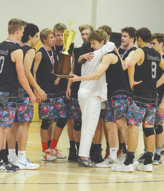 Senior Parker Mikesch hugs Beavercreek boys volleyball coach Carol Bysek, while hanging onto the team's trophy during the Ohio Division I boys high school volleyball tournament, at Capital University in Columbus.
