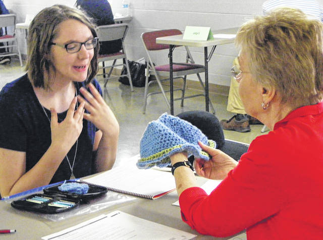 Submitted photos Elizabeth Montgomery talks to judge about her knitting-crocheting project.