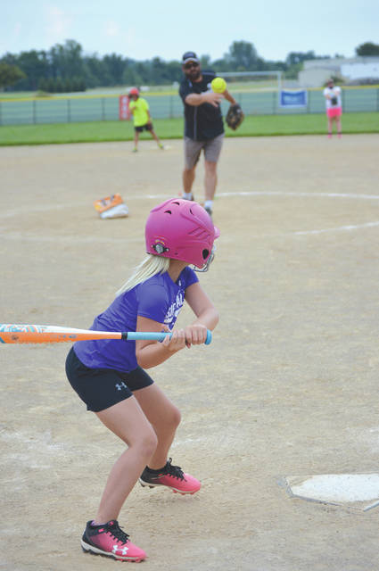 A member of the Jamestown 8U Lime softball coaches pitch team readies to swing at a pitch thrown by coach Clint Conner, during practice July 10 at Seaman Park in Jamestown. The park will host the Ram-Page All-Star Tournament on Saturday and Sunday for area 8U and 10U baseball and softball teams.