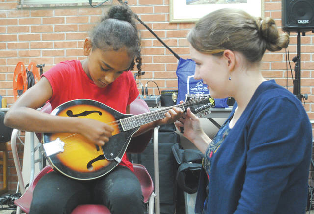 """The band members explained how each instrument works and, following the performance, offered a """"musical petting zoo"""" in which children were invited to play and strum the bass, fiddle, mandolin, banjo and guitar."""