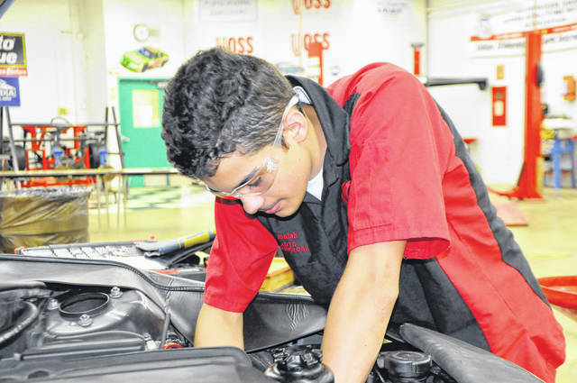 Isaiah Estep, a senior automotive technology student from Fairborn, begins the process of replacing the water pump on a BMW crossover.