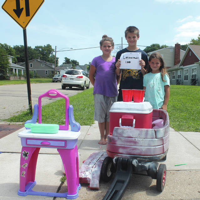 Anna Bolton   Greene County News Siblings Neveah Colquhoun, 9, Braiden Mattox, 12, and Brianna Caplinger, 6, sell pink lemonade from their neighborhood lemonade stand at the corner of North Columbus and East Market Street Aug. 9. The trio is selling $1 lemonade and candy every day until school starts.