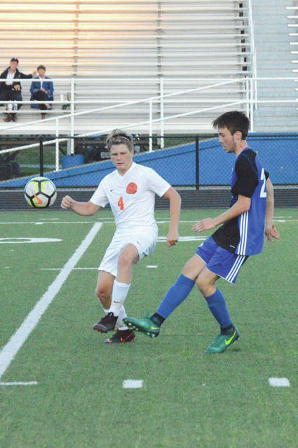 Xenia's Zach Stefan (right) gets off a shot as Wilmington's Josh Vaughan defends. Both players scored in the Aug. 23 boys high school varsity soccer match at Doug Adams Stadium in Xenia, and Wilmington won 3-1.