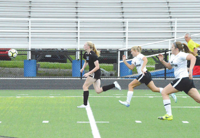Xenia senior forward Taylor Huffman (20) outraces the Lynchburg Clay defense for an eventual goal, during Friday Night Futbol, Aug. 17 at Doug Adams Stadium. The host Buccaneers rallied to claim a 3-2 season opening win.